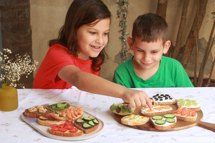 איך לגרום לילדים לאכול מגוון | ילד מול מגשי סנדוויצ׳ים | סנדוויץ׳ לבית ספר | מסיבת סנדוויצ׳ים לילדים | הבלוג של נעמה מגשימת מתנות | naamasimanim.co.il